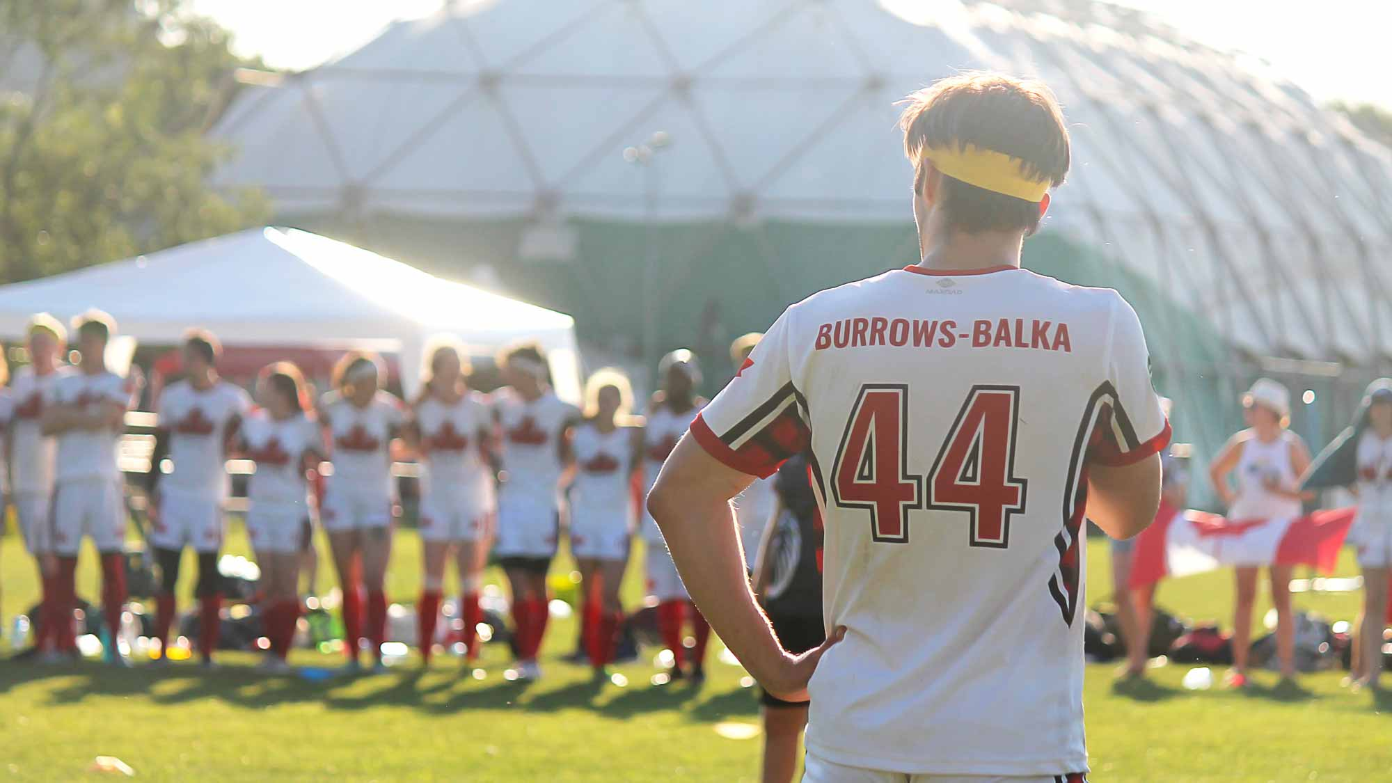 Photo of Quidditch Canada player in light jersey from the back.